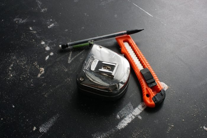 overhead view of a chrome tape measure, lead pencil and a retractable knife