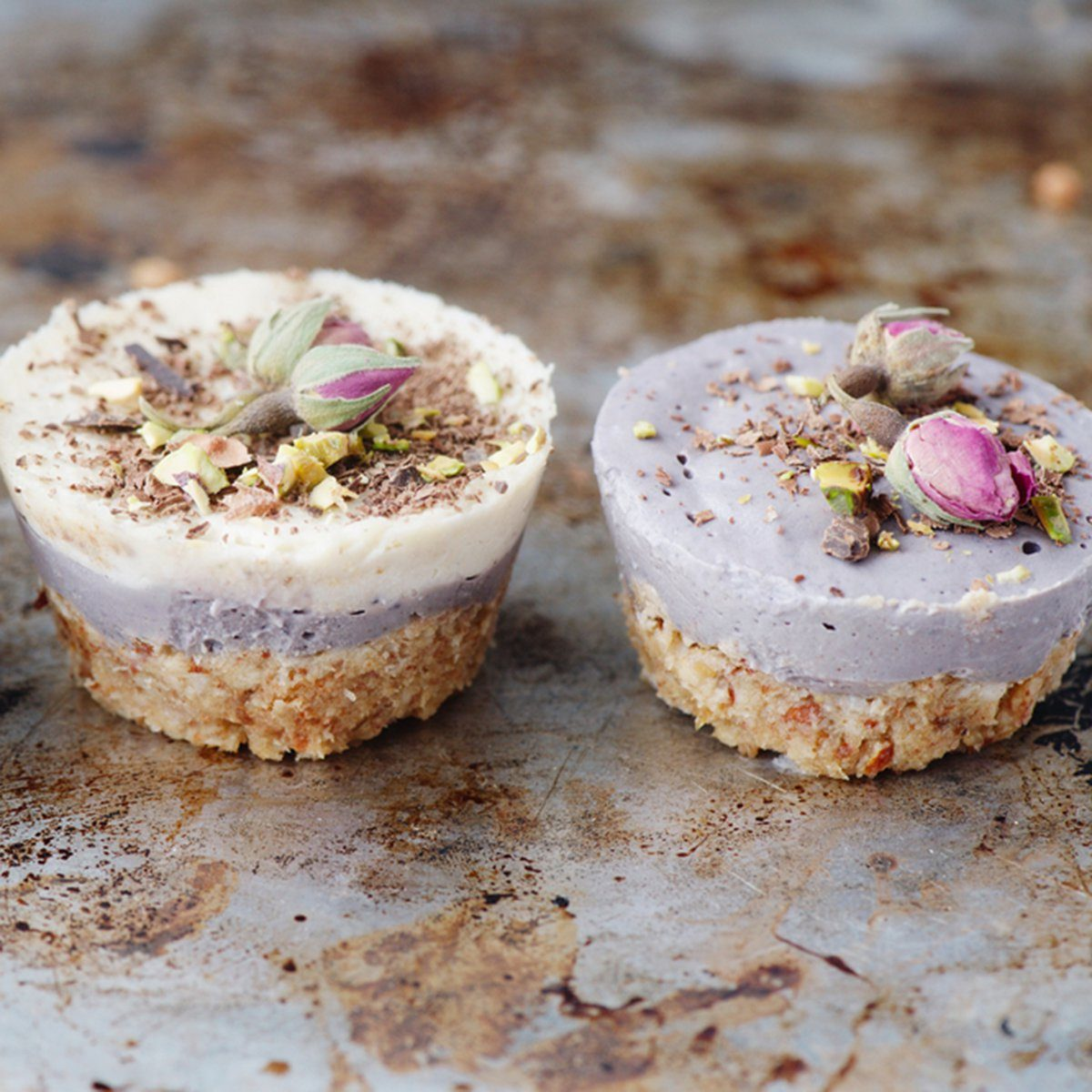 Vegan mini cheesecakes with blueberry and white chocolate layer with adding of cashews, cacao butter and coconut milk, and base made of almonds, shredded coconut and medjool dates