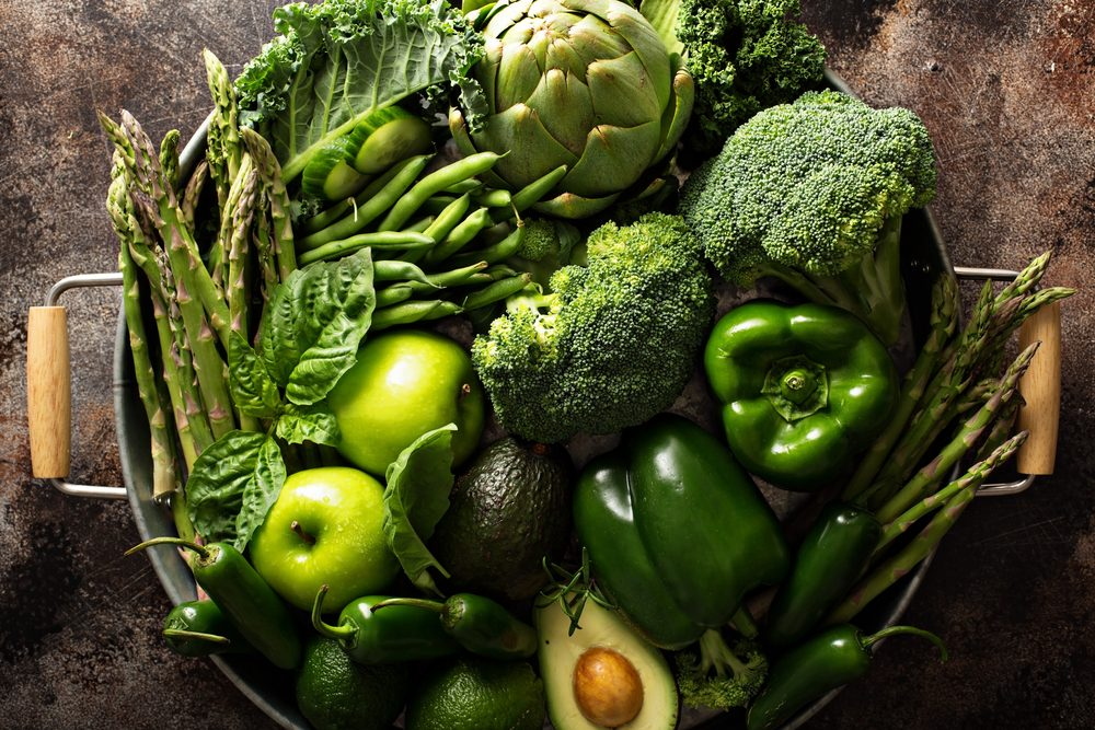 Variety of green vegetables and fruits on a tray, dark setting overhead shot