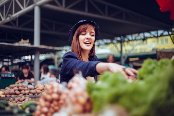 Young Female Looking For Some Vegetables At Market Place