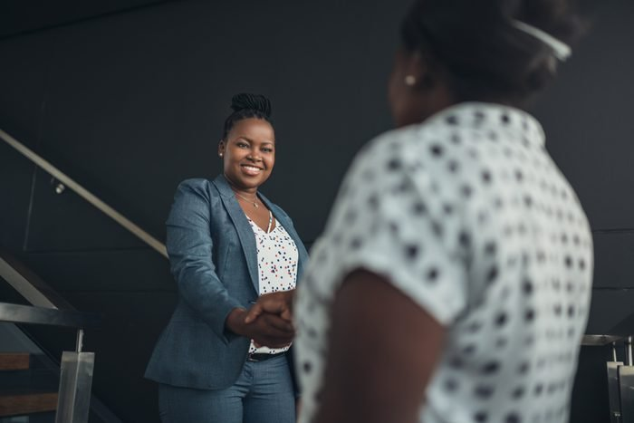Executive african american woman shaking hands with welcoming smile