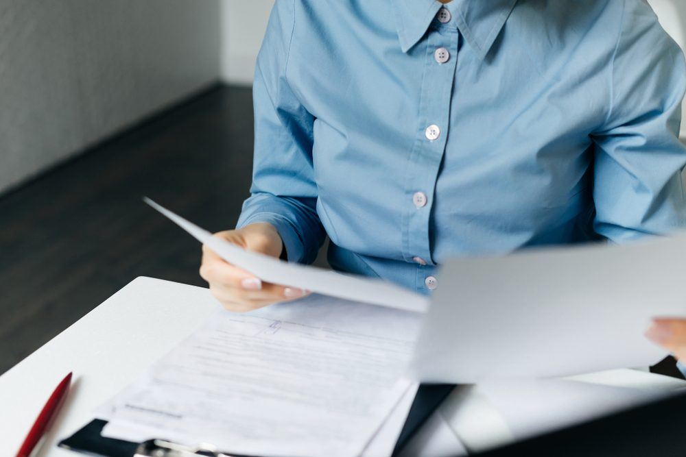 business woman in blue shirt examines important documents