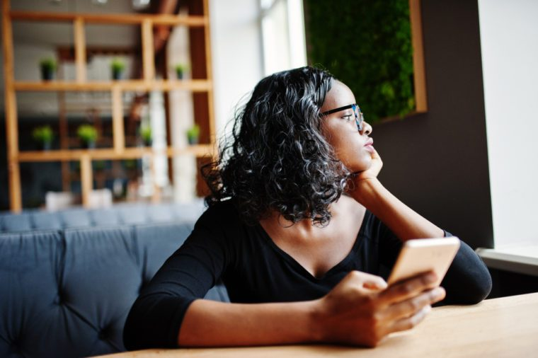 African american girl in sunglasses sitting at cafe and holding mobile phone at hand.