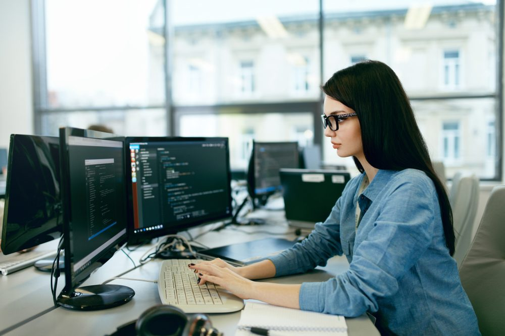 Young Woman Working And Programming On Computer In Office. Beautiful Female Programmer Working Looking At Monitor, Typing Data Code In Company Office. High Quality Image.