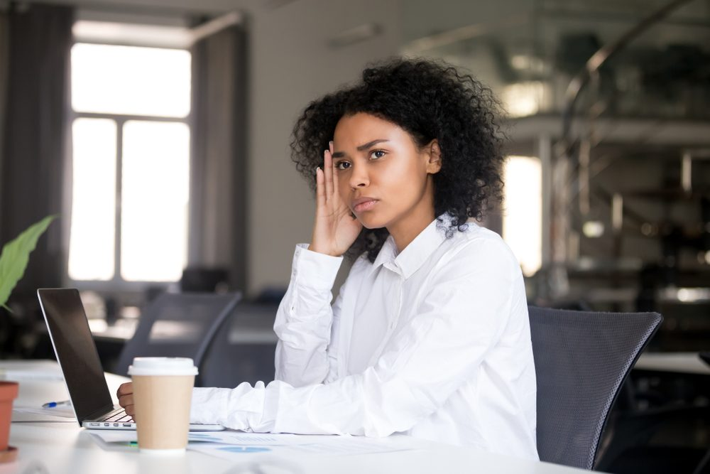 Serious thoughtful african business woman sitting at office desk with laptop looking away thinking of problem solution, pensive millennial black female searching new idea at work lost in thoughts
