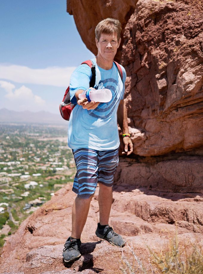 Man gives water to hikers on Camelback Mountain in Phoenix, Arizona.