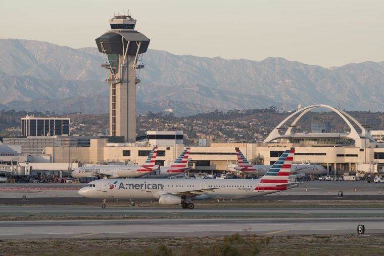 EL SEGUNDO, CA, USA - JANUARY 21, 2018: American Airlines planes at the Los Angeles International airport (LAX) with the San Gabriel mountains in the background.