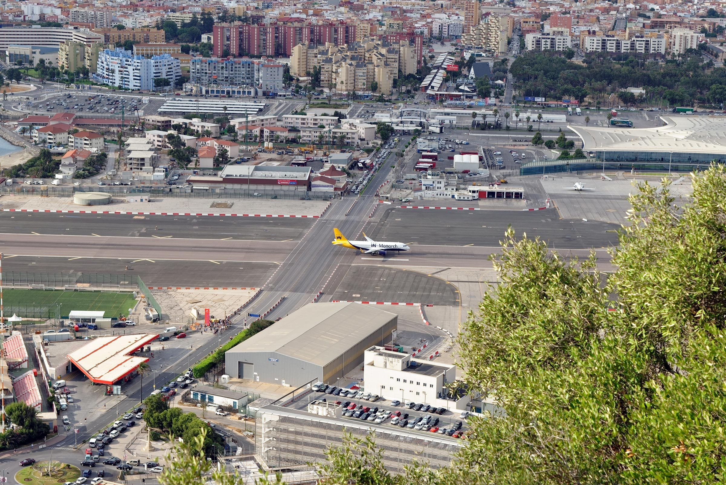 GIBRALTAR - AUGUST 29, 2017: City of Gibraltar, the airport runway with a landed Monarch airplane and La Linea de la Concepcion in Spain.