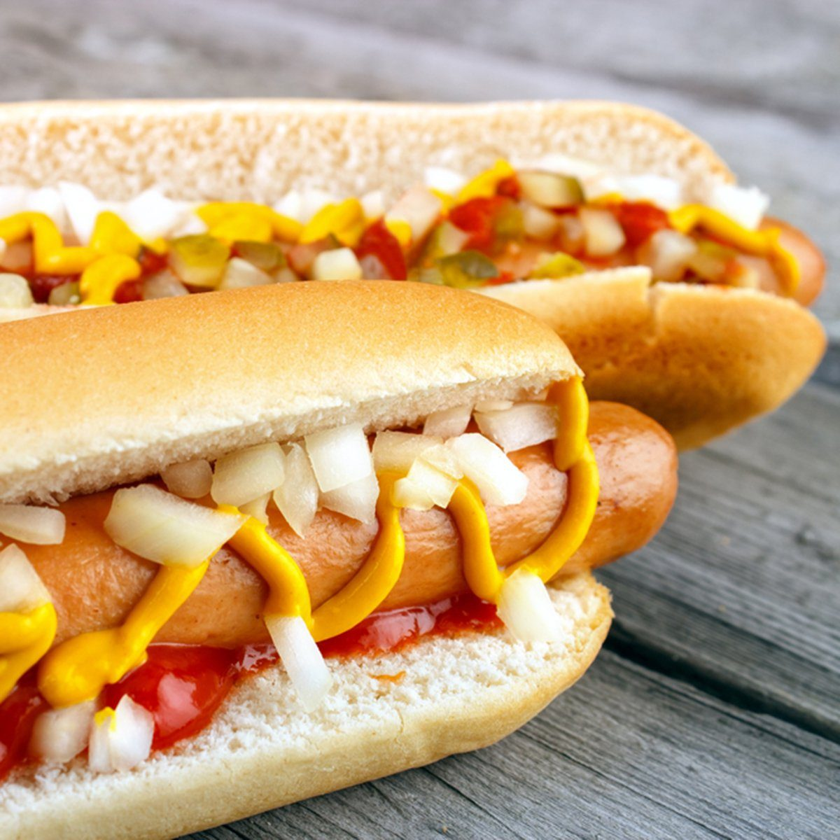Two hot dogs with ketchup closeup , yellow mustard and onion on gray wooden surface; Shutterstock ID 263142953; Job (TFH, TOH, RD, BNB, CWM, CM): TOH