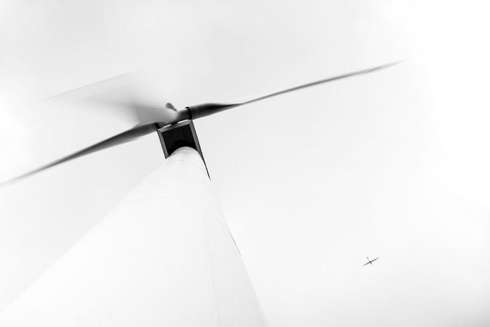View from below of large electric environmentally friendly wind turbine with aeroplane flying high in the sky - unusual angle
