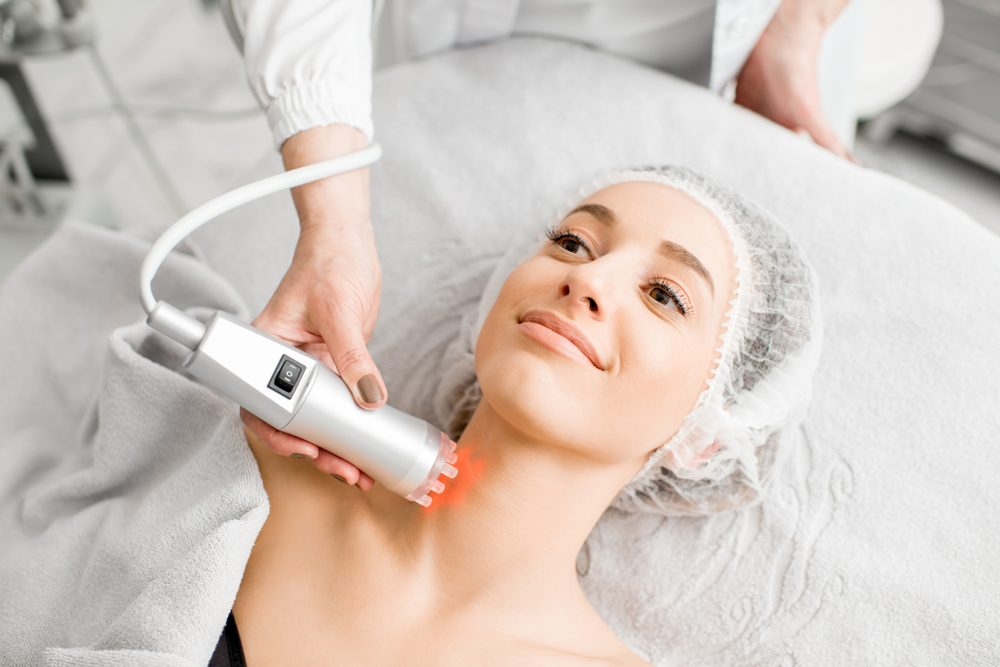 Young woman during a massage on the neck with professional tool at the medical center