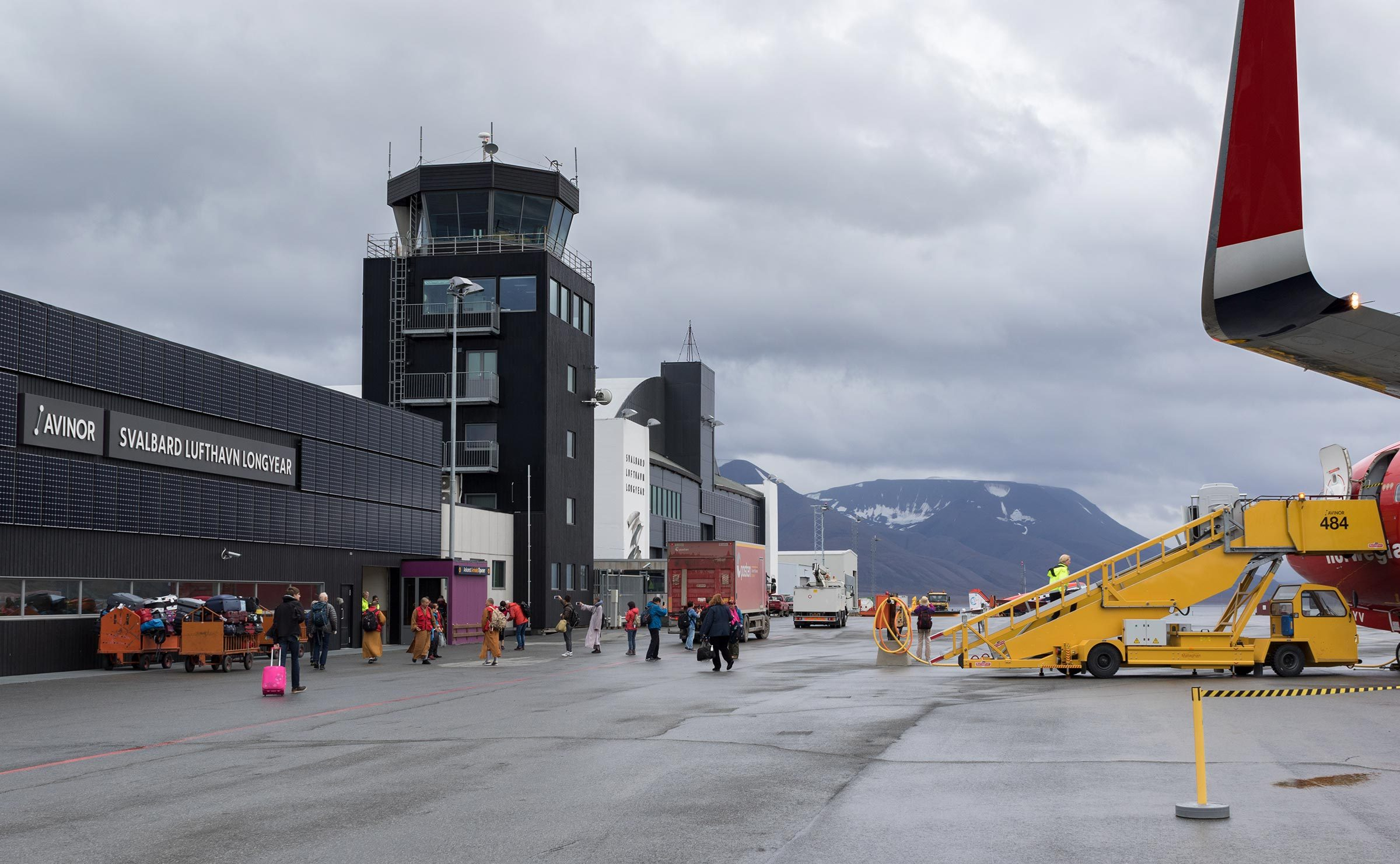 Longyearbyen, Svalbard - August 2017: Passengers disembark from Norwegian aircraft at the Svalbard airport Longyear (LYR) - northernmost airport in the world with public scheduled flights.