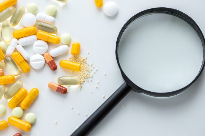 Magnifying glass controlling white and yellow pills, tablets and capsule for medicine side effects and ingredients