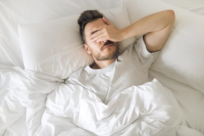 man sleep tired bed sheets