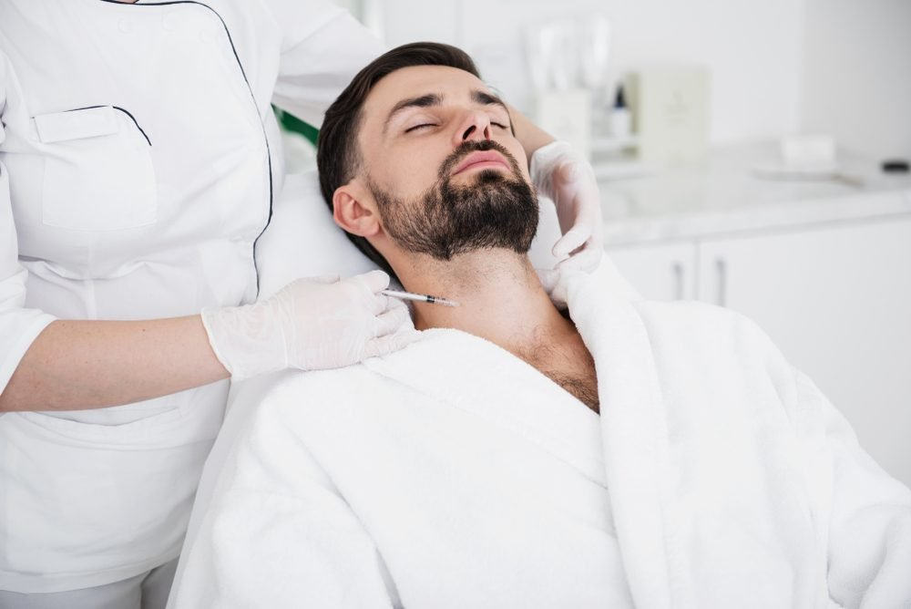 Man in white bathrobe staying calm while experienced cosmetologist in rubber gloves carefully touching his neck and making an injection