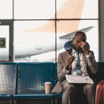 sleepy businessman with travel pillow and newspaper waiting for flight at airport lobby