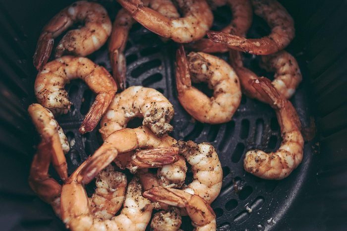 Roasted shrimps with garlic and herbs. Seafood, shelfish. Shrimps Prawns grilled with spices and garlic on black stone background, copy space. Shrimps prawns on cast iron pan.