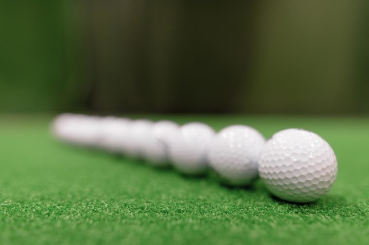 Close Up Shot Of Golf Balls Scattered Around On Green Surface