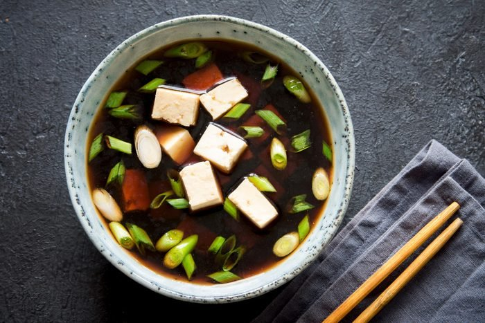 Japanese miso soup in ceramic bowl on dark background, copy space. Asian miso soup with tofu.