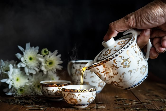 Hand pouring tea from porcelain tea pot to porcelian tea cup on wooden table with white Chrysanthemum flowers with dark smoky background