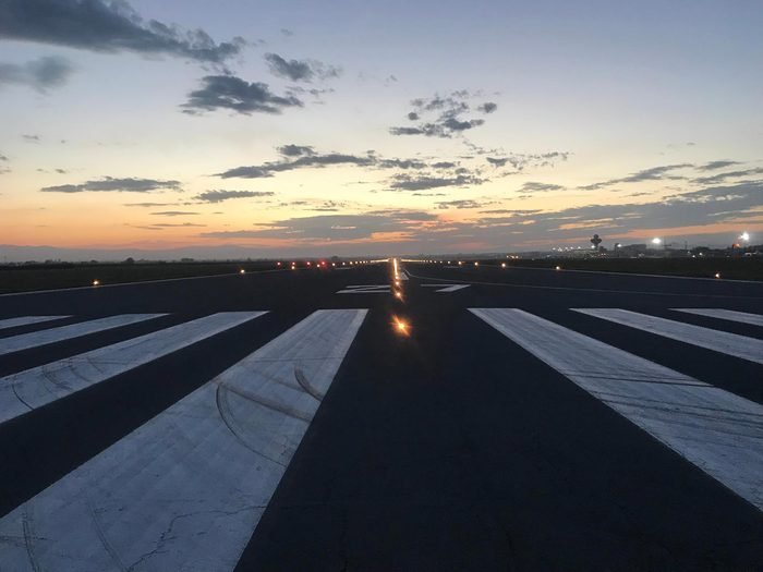 Photos of Airport Runways at twilight, showing runway markings, runway lights, clear skies and mountains in the horizon