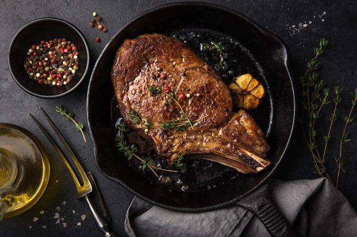 beef steak on cast iron pan, dark background, top view