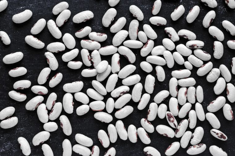 Dry white common beans with red blotches evenly spread on dark blue background. Full frame shot from above