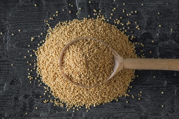 A pile of amaranth seeds and a wooden spoon on a dark wooden table. The view from the top.
