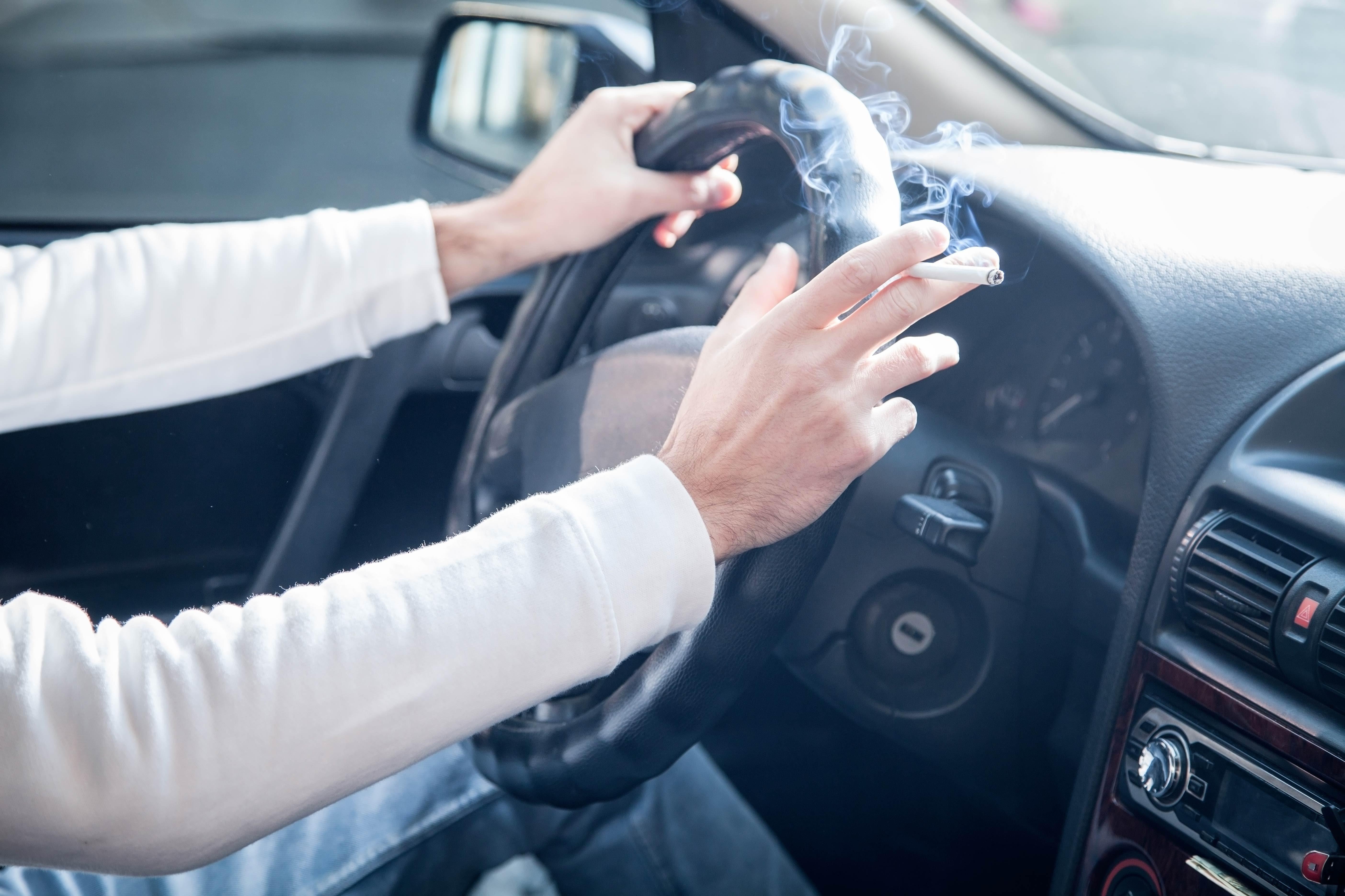 Man smoking cigarette driving