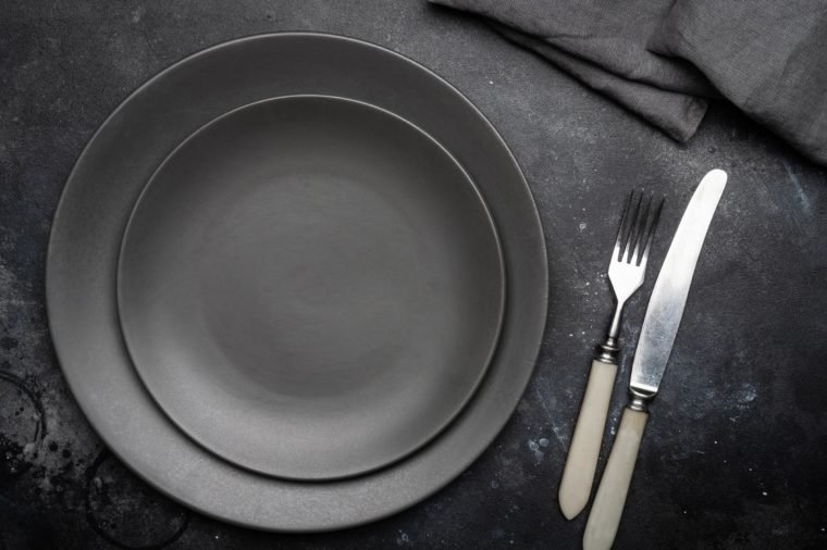 Empty gray plate (ceramic) on a dark gray background with a knife and fork, decorated with a bouquet of lavender and a napkin. Gray minimalistic concept. Copy space.
