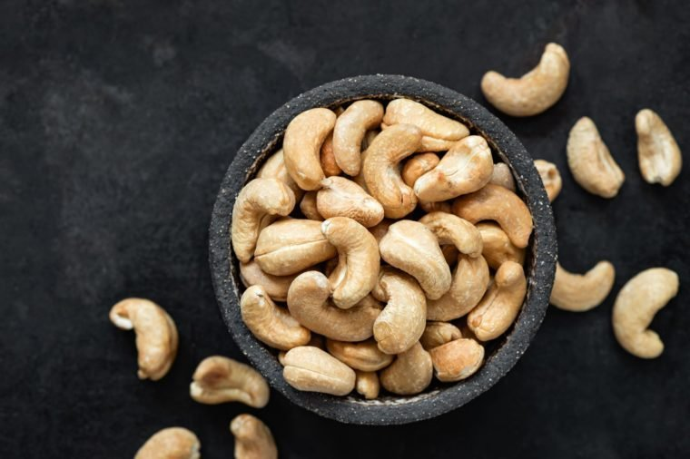 Cashew nuts in bowl on black background. Top view, copy space for text. Healthy snack, vegetarian food, beer snack
