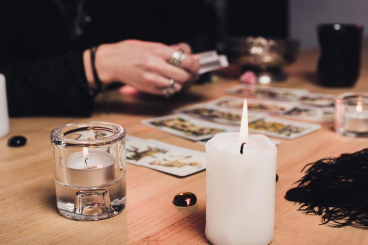 selective focus of burning candles with female psychic on background