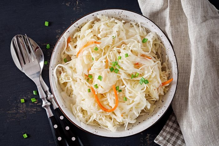 Fermented cabbage. Vegan food. Sauerkraut with carrot and spices in bowl on the dark background. Trend food. Top view . Flat lay, copy space