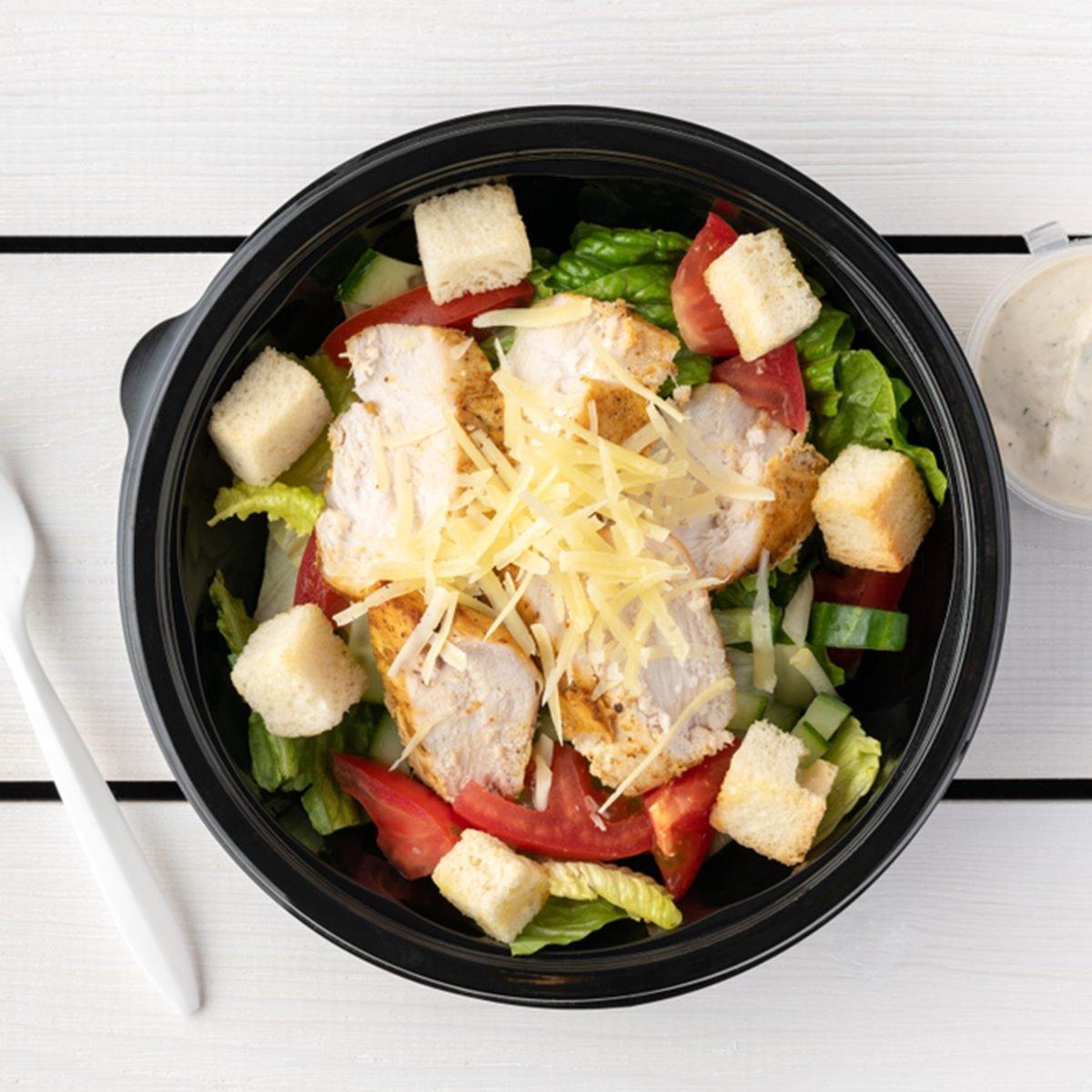 Caesar salad in round black lunchbox on wooden bacground; Shutterstock ID 1315532318; Job (TFH, TOH, RD, BNB, CWM, CM): TOH