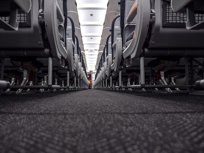 View down the aisle of an airplane before the first flight of the day taken from a low angle. The captain does his preflight safety checks at the very front of the plane