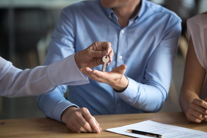 Close up man receiving keys from new house, making deal with realtor in office, tenant signing lease agreement with mature manager, taking loan or mortgage, client purchasing property, real estate
