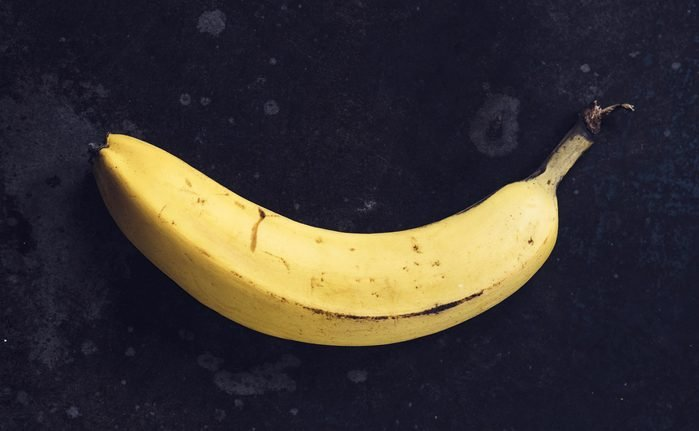 Ripe yellow bananas fruits, bunch of ripe bananas with dark spots on a dark background