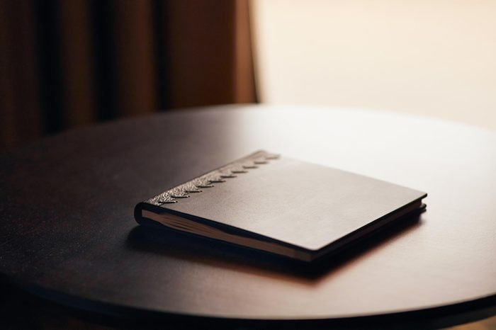 Note book with hard wooden cover on table by the window in natural light
