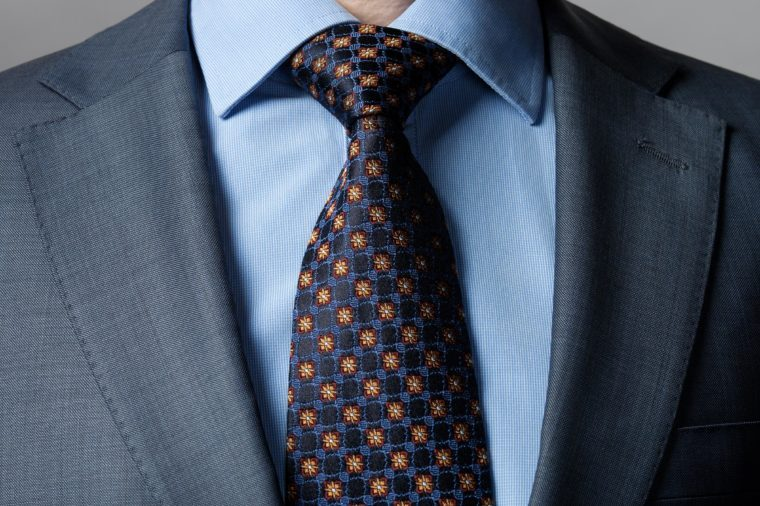 Elegant businessman wearing formal suit and tie, dark background
