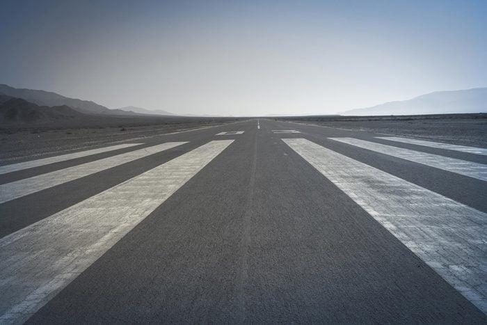 Long paved runway shot from its threshold markings