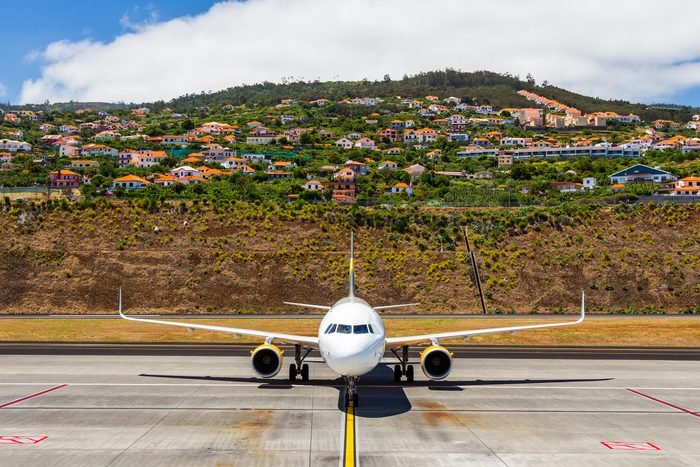 Aircraft at the airport after landing, preparing to be docked, in the background Agua de Pena village, Madeira, Portugal