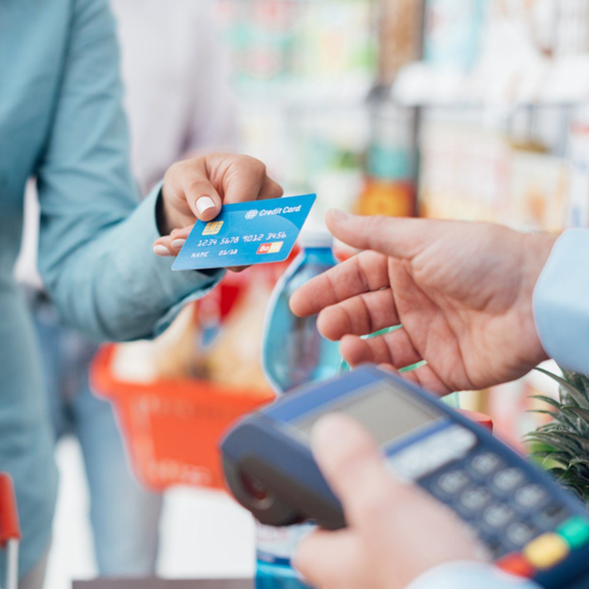 Woman at the supermarket checkout, she is paying using a credit card, shopping and retail concept; Shutterstock ID 503419588