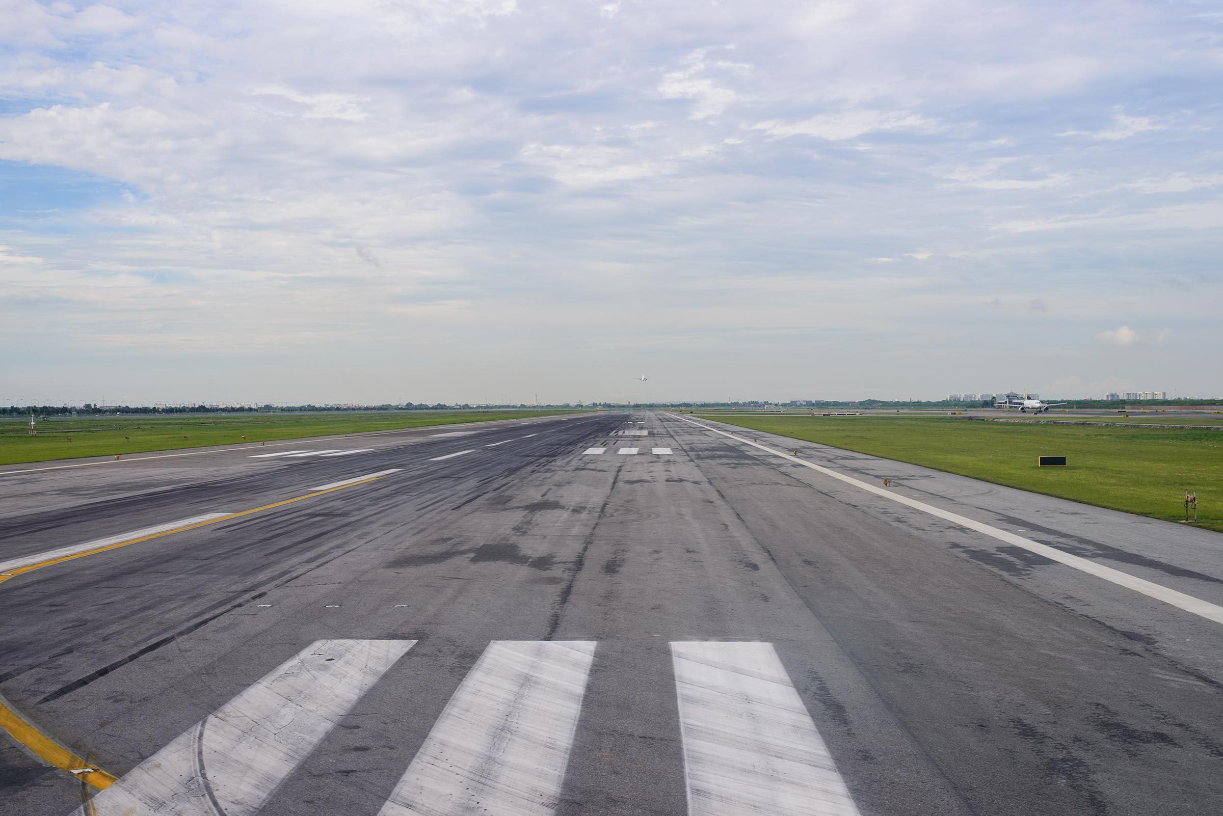 Runway of an airport. An airplane just took off in the background