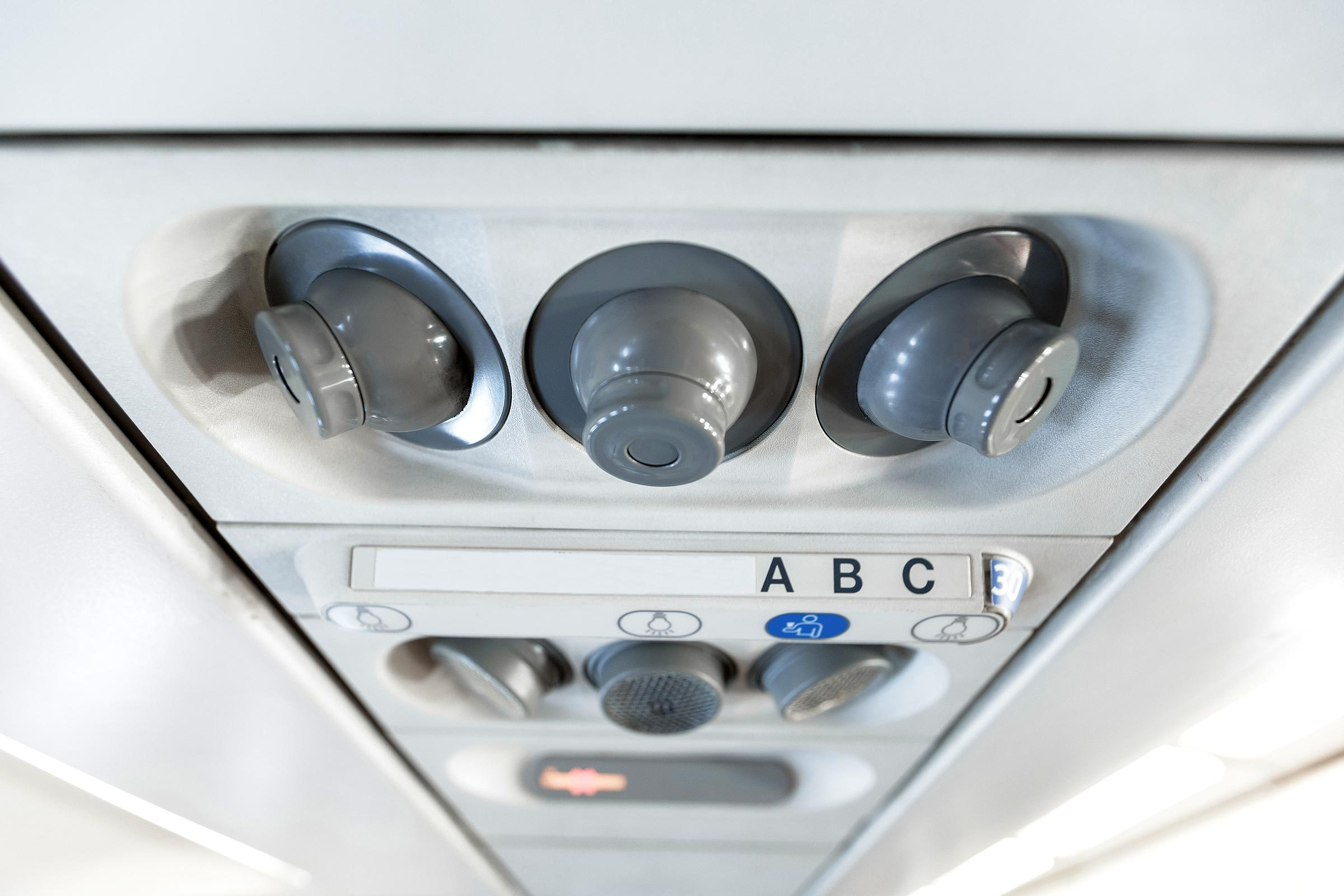 Overhead console in the modern passenger aircraft. air conditioner button and lighting switch