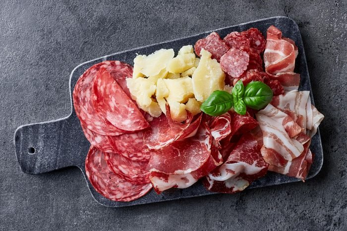 Marble cutting board with prosciutto, bacon, salami and cheese on dark stone background. From top view