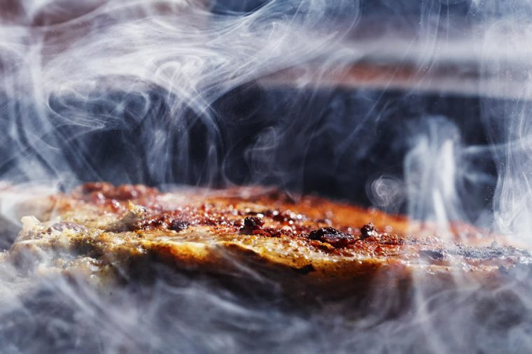 smoke and steam rise from a pork steak