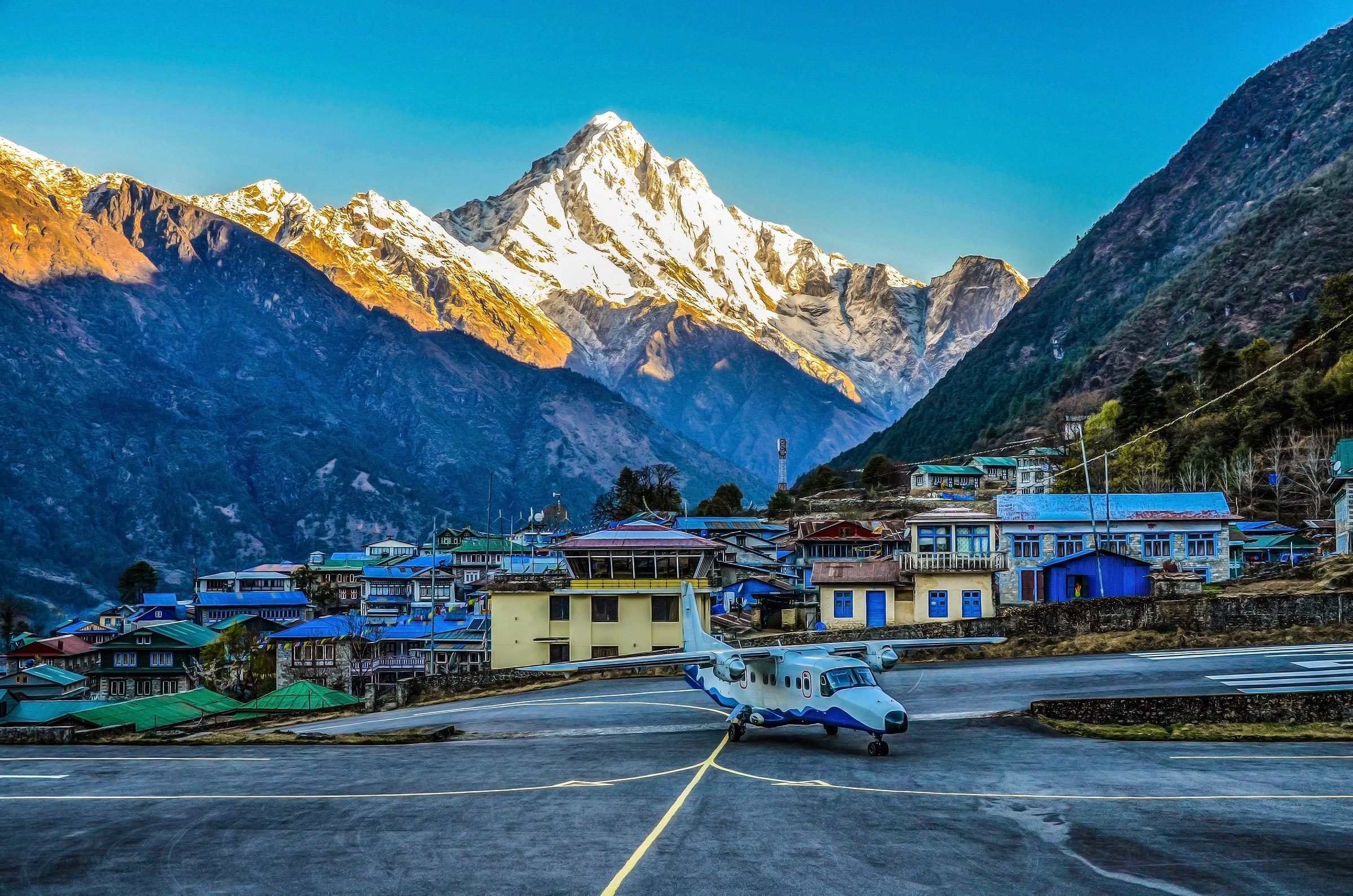 Airport in Lukla with plane and mountains behind