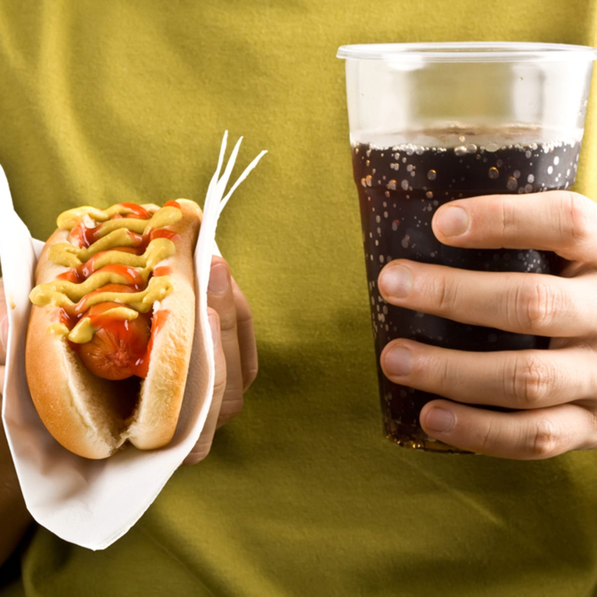 classic hot dog with mustard and ketchup and cola holding in hands; Shutterstock ID 68139490; Job (TFH, TOH, RD, BNB, CWM, CM): TOH