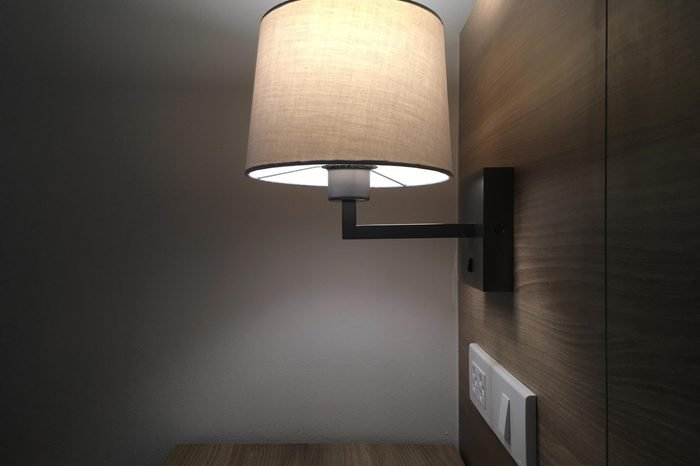 Lamp on a night table next to a bed