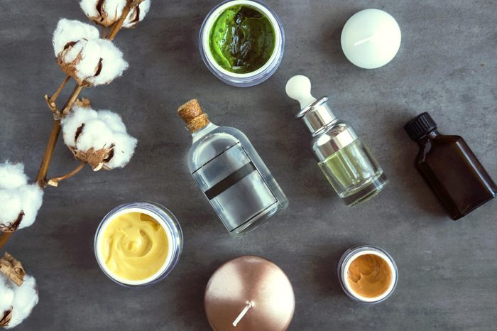 SPA cosmetic products on dark table from above. Coconut, argan oils, organic creams and serums. Beauty blog flatlay